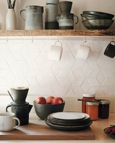 Cain's stoneware, shown here, consists of necessary tools for their daily routine, including coffee-brewing. The countertops are quartz composite from a local company. Cain learned how to fire the ceramic tiles herself to form the geometric backsplash.