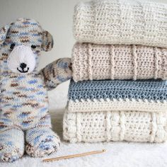 Looks like this mischievous bear is trying to knock over my blanket pile :-) -  Thank you again for our wonderful bear @maryanneliguori  Isn't he the cutest!!! -  My baby blankets pictured from the top down: Ivory Dawn January Snuggles a new design coming soon(!) and Sweet Haven. -  #babyblanket #HiddenMeadowCrochet #crochettexture
