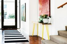 Stripe runner and modern table with yellow hairpin legs.