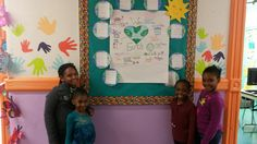 """Students at NYC Eco-School PS 361 in Brooklyn in front of their """"We Love Earth """" bulletin board. Display was created by Ms. Goldberg (Speech and Language Specialist)."""