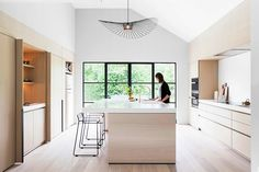 This modern light wood kitchen features black accents, white countertops, a large island, foldaway cabinet doors, and a pantry with hidden lighting. White Countertops, Kitchen Decor, House Design, Home Decor Kitchen, Light Wood Kitchens, Home, Contemporary House, Minimalist Home, Modern Kitchen Window