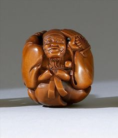"""WOOD NETSUKE 20th Century By Hideyuki. Depicting a Sambaso dancer with fan and rattle. Signed and seal marked. Height 1.5"""" (3.5 cm)."""