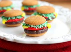 Mini Burger Cookies from The Girl Who Ate Everything - Two vanilla wafer cookies, 1 Thin Mint or grasshopper fudge cookie, green dyed coconut, and red and yellow decorator frosting...Great for summertime and so simple!!