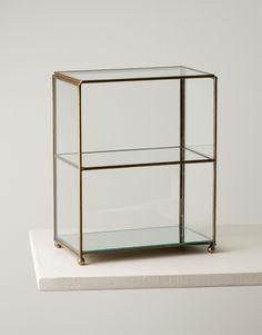 Elegant litet skåp i glas för dina smycken eller parfymflaskor. Skåpets alla sidor samt hyllplan är helt i glas och fogarna i mässing. Skåpet har en spegel i bo