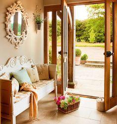 Recibidor en casa de campo con banco clásico, espejo barroco, cesto y cojines.