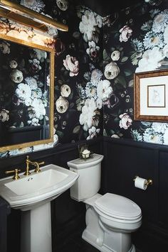 Ellie Cashman Dark Floral Wallpaper covers the upper walls of this gorgeous powder room lined with black wainscoting and fitted with a pedestal sink finished with a brass vintage faucet kit fixed beneath a gold leaf mirror lit by a brass picture light.