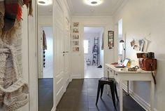 czarny metalowy taboret,czarne kwadratowe płytki na podłodze,białe biurko skandynawskie,duże lustro prostokatne na ścianie w aranżacji przedpokoju