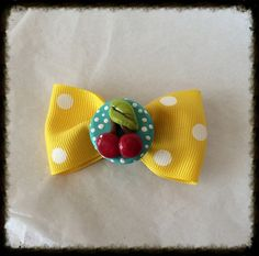 """Very Cherries hair bow   This Darling little bow Is a perfect accessory for any pinup or rockabilly wardrobe. I started it off with yellow polkadot  Grossgrain Ribbon. In the center I added one of my own polymer clay cherries cabochons. This bow measures about 2 1/2"""" across and the clip has..."""