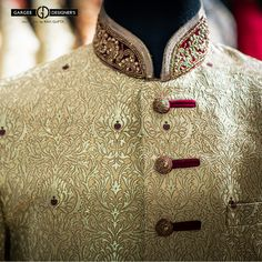 The gold imperial sherwani is finely crafted for the groom in charge. With Rich Indian embroidery at collar & buttons, it is a subtle choice for a tasteful man.