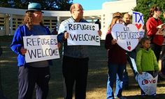 Humanity at work yet again despite all the noise in Texas and Indiana: Human rights activists hold placards welcoming refugees to Dallas, and all of Texas, on 21 November.