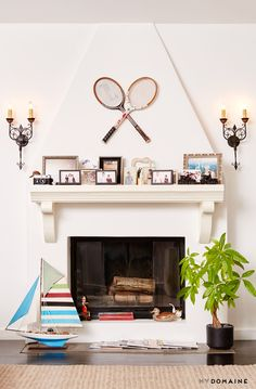 Tennis rackets hung over fireplace with styled mantle full of framed photos