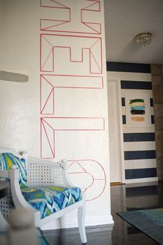 """""""HELLO"""" with yarn/nails in the entry. Super fun. (Love the stripes on the next wall, too.)"""