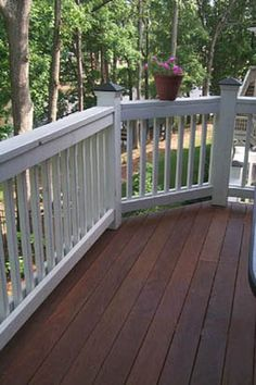 White railing around timber deck. Gotta stain our porch the dark wood to match the inside floors. Beautiful.