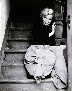 Milton H. Greene, Marilyn Monroe, Seated on a Wooden Staircase Wearing a Peasant Skirt