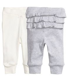 Light gray melange. CONSCIOUS. Pants in ribbed organic cotton jersey with three rows of ruffles at back. Elasticized waistband and ribbed hems.