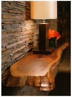 Stone veneer with rough cut wood ledge. Inspiration for fireplace and mantle redesign.