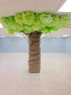 Great idea for a basement! Turned a pillar into a tree by cutting and taping pool noodles together to form branches, wrapping crumpled kraft paper around the trunk and branches, and hanging homemade pompoms as the leaves.