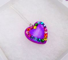 A puffy heart shaped charm pendant, made from layers of clear casting resin, which is then varnished and sanded in order to give a smooth glossy finish. Carefully filled with brightly coloured purple glitter and adorned with rainbow coloured Swarovski crystals, a perfect addition to any quirky jewellery collection!  Your charm will be lovingly placed on a 16 inch silver plated chain and will fall just beneath the collarbone. If you would like the chain to be lengthened please let me know in…