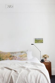 An Edwardian home in Melbourne is given a fresh new interior: The serene bedroom is peppered with soft, artful touches like a small vintage painting and a painterly cushion by Geneviève Lévy from Manon. A copper vase and sleek Luminara 'Daphine' table lamp from ECC Lighting+Furniture keeps the look contemporary.