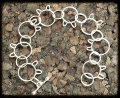 Classic Kitty Bracelet   The perfect gift for the cat lover in your life.  Handcrafted kitty heads with 18 gauge, 16 mm Argentium Silver and connect with 10 mm circles.          Retail:  $100.00  Sale:      $60.00