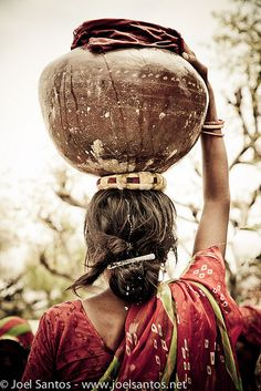 Carrying the Load. A women in India carrying water in a pot balanced on her head. Sometimes they even balance another pot on their hips simultaneously. In some rural areas water is fetched from a well or a river. In olden times even milk, butter, etc were carried in the same fashion. Even today in the cities men and women who sell vegetables and fruits door to door, use the same mode carrying their ware in shallow baskets.