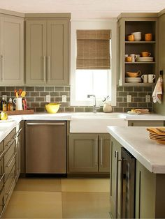Give your cabinets a new look in little time with a fresh coat of paint. Muted colors inspired by nature add modern appeal to this cottage-style kitchen. The greenish-gray hue of the cabinetry expertly coordinates with the subway-tile backsplash and stained concrete countertops.