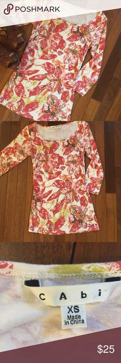 """Floral CAbi Tunic Top Size XS Floral 3/4 length sleeve Tunic Top.  Wide scoop neck or Boatneck depending on how you wear it .  Slight ruching at waist .  Very flattering fit .  Can be worn over leggings or worn jeans .  Cute with a demon skirt or shorts too.  Size XS measures shoulder to hem 25.5"""", armpit to armpit 14"""", waist 12"""".  Bundle 2+ and Save 20% CAbi Tops Tunics"""