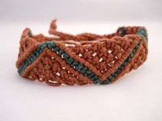 """This zig-zag macrame cuff is handcrafted using brown and forest green hemp. It is made with a zig zag pattern in forest green. This bracelet is just under an inch wide and has braided ends that you can tie on to ensure a custom fit.  Length: 12"""" (end to end)"""