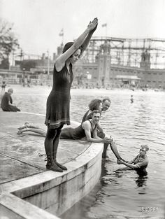 "Starlight Park, the Bronx, ca. 1921 // This photograph showcases a variety of swimming costumes from the early The young girl wears a wool swim dress with stockings and lace-up shoes known as ""beach boots""."
