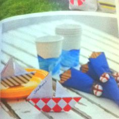 Captain's Table  Make place settings for your passengers.  Dip a sponge in blue paint and swipe around the cup to create a wave pattern.  Draw lines on a Lifesaver with edible markers. Tie onto napkins with twine.  Fold simple origami boats to make place cards. Visit origami-make.com for instructions on how to create them.  Parents magazine May 2012 pg. 71 Origami Frog, Origami Bird, Origami Flowers, Useful Origami, Origami Easy, Nautical Place Cards, Origami Boat Instructions, Origami Heart With Wings, Origami Decoration