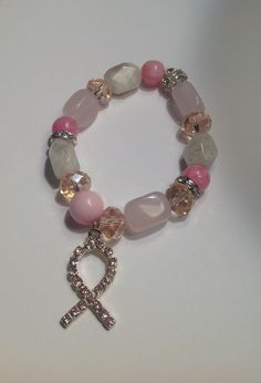 Beautiful Breast Cancer Awareness Bracelet. made with a mixture of pink and pale colored beads finished with a pink rhinestone ribbon charm.   Handmade chunky beaded jewelry made by Madelyn & Ruby Jewelry Co.  This bracelet is approximately 7 ¼ inches .  Thanks for looking. Please contact m...