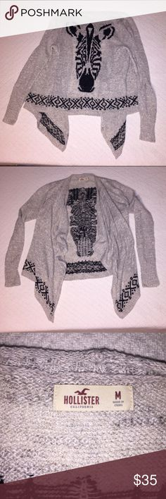 Hollister Medium Tribal Zebra cardigan Hollister Medium Tribal Zebra cardigan. Excellent like new condition. Warm, soft and cozy. Heather Oatmeal (kind of a light grey and cream mix) color with black knitted tribal patterns and zebra. Has a tapered cut so front is longer. This was a popular cardigan that sold out. I only wore this once because cardigans with the tapered front look odd on me with my super short legs. Hollister Sweaters Cardigans