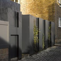 Climbing plants grow in the recesses of this mysterious steel fence, which conceals the entrance to a renovated coach house in north London.