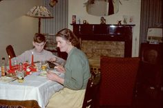 Printed colour photograph of Muriel Scagell and her son Robin eating Christmas dinner in the dining room of 1 Milverton Drive, Ickenham, Middlesex. The photograph was taken by Gordon Scagell on 25/12/1958. This is a copy made from the original colour Kodachrome transparency for the Geffrye Museum in 2009, and is one item in the Documenting Homes collection (150/2010-1 to –43) from Andrea Scagell.
