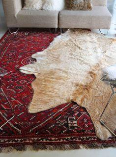 layering rugs cowhide over Turkish via cheetahisthenewblack