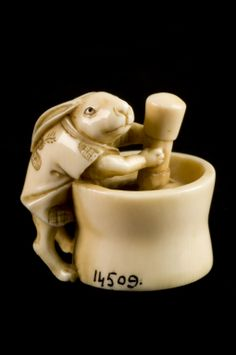 This ivory netsuke was made in Japan. It is in the form of a rabbit-like creature grinding with a mortar and pestle. This imagery almost certainly refers to the 'Hare in the Moon', a messenger of the moon deity. The creature mixes the elixir of immortality with his mortar and pestle.