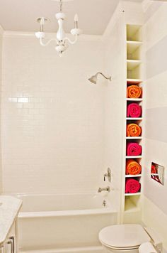 15 Incredible Small Bathroom Decorating Ideas - minimalist white bathroom with a. 15 Incredible Small Bathroom Decorating Ideas - minimalist white bathroom with a white chandelier + bright pop colored towels Bathroom Storage Solutions, Small Bathroom Storage, Bathroom Design Small, Small Bathrooms, White Bathrooms, Bathroom Organization, Beach Towel Storage, Small Bathroom With Tub, Bathrooms Decor
