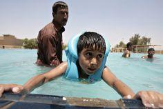 El Instructor de natación Abbas Khalid (L), de 35 años, asiste a un niño iraquí durante una clase de natación en una piscina pública en el centro de Bagdad