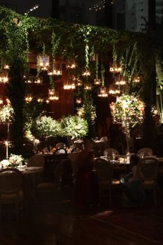 not the centerpieces, but the hanging glow of lanterns plus mossy green all over and hanging down. rustic meets midsummer nights dream