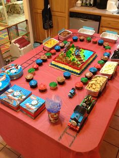 Table for Thomas party: cake from BJs, homemade red, green, brown and blue cupcakes, gravel (popcorn) car, coal (rice krispie treats), aquarium (goldfish crackers) car, produce (broccoli, carrots and peppers) car, dairy (dip) car, zoo (animal cracker) car, and lumber (pretzel stick) car.