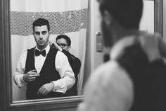 Groom fixes his shirt on the morning of his wedding day at the Belvedere Hotel in Baltimore, MD. Captured by NYC wedding photographer Ben La...