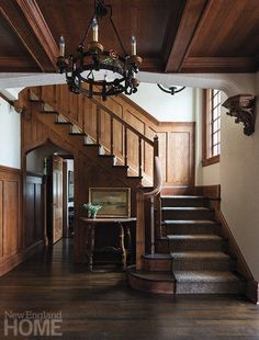 The entry's original woodwork and chandelier are testaments to the home's pedigreed past. Atop the antique table rests an 1899 painting of Lake George, New York, bought at an auction. Homeowner, House, Home, Old Greenwich, Tudor, Tudor Style Homes, New England Homes, Stairs, House And Home Magazine
