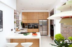 u-förmige Küche mit Holzfronten und weißen Arbeitsplatten