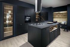 Donkerkleurige keuken met houtaccenten. Deze moderne keuken heeft als hoofdkleur een zeer donkerblauw tot zwarte tint. Door gebruik van lichte houtaccent krijgt de keuken toch een lichte en warme toets. Het kookeiland is voorzien van een gasvuur met een cilindervormige dampkamp als extra design element. De deurfronten van deze keuken bestaan uit een subtiele kaderdeur. Aan één muur zijn er verschillende planken geplaatst om keukenspullen en decoratie te plaatsen.