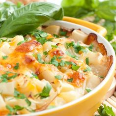 A Delicious recipe for potato cheese bake topped with parsley and served with fresh basil leaves.