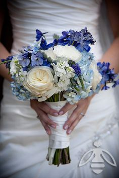 Bridal bouquet featuring shades of blue hydrangea, delphinium, veronica, garden roses, and dusty miller.