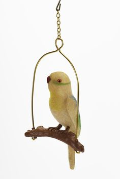 Ornament in form of a bird of flocked plastic, possibly a budgerigar, on a swing made of gold-coloured wire and brown plastic hanging from a hook and short chain.