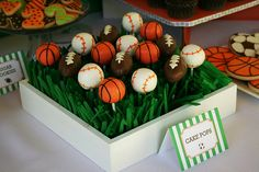 Baseball cake pops standing on a bed of fake grass.