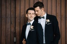 Gay wedding photo of the two grooms in front of an old wooden building