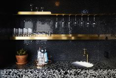 Black was a natural choice when it came to updating an already existing wet bar. The brass shelf was laser-cut from thick brass sheet--designed with a simple geometry as a nod to a classic bar.